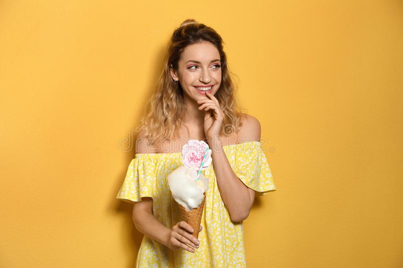 Portrait of young woman holding cotton candy dessert on background royalty free stock photography