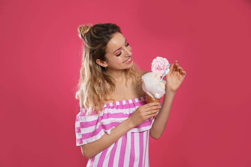 Portrait of young woman holding cotton candy dessert on background stock images