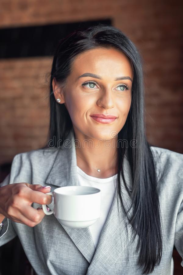 Portrait of young woman is holding cup of coffee, smiling at coffee shop cafe royalty free stock photography