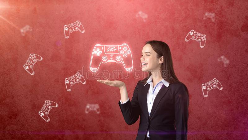 Portrait of young woman holding gamer`s joystick on the open hand palm, over drawn studio background. Business concept. Portrait of young longhair brunette royalty free stock photos
