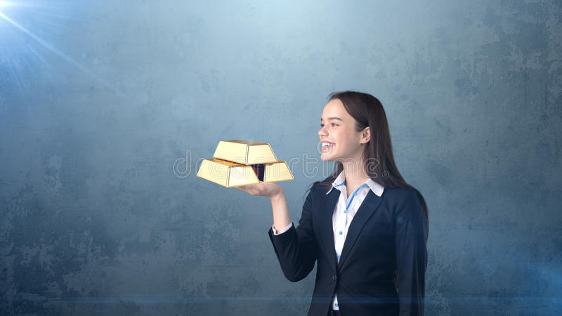 Portrait of young woman holding golden bars on the open hand palm, over isolated studio background. Business concept. royalty free stock photography