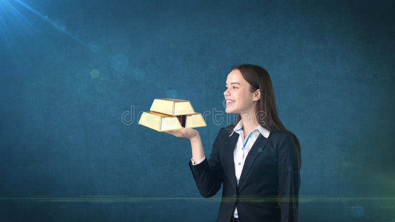Portrait of young woman holding golden bars on the open hand palm, over isolated studio background. Business concept. royalty free stock photos
