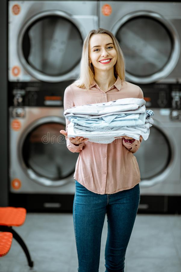 Woman with ironed clothes in the laundry. Portrait of a young woman holding ironed clothes in the professional laundry with drying machines on the background stock photography
