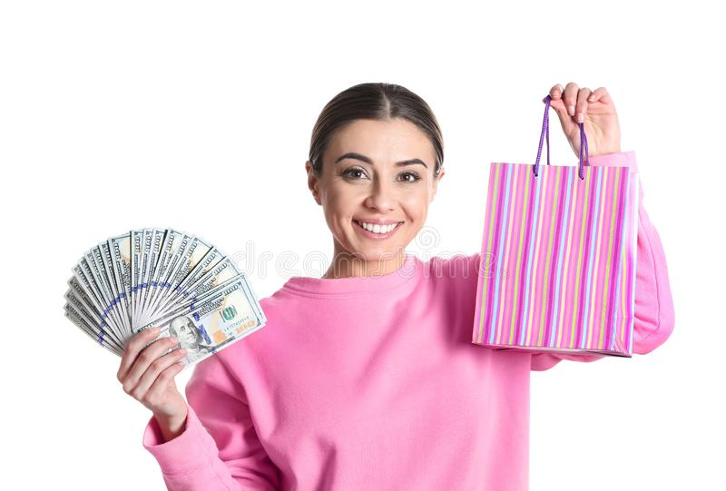 Portrait of young woman holding money banknotes and shopping bag on white stock images