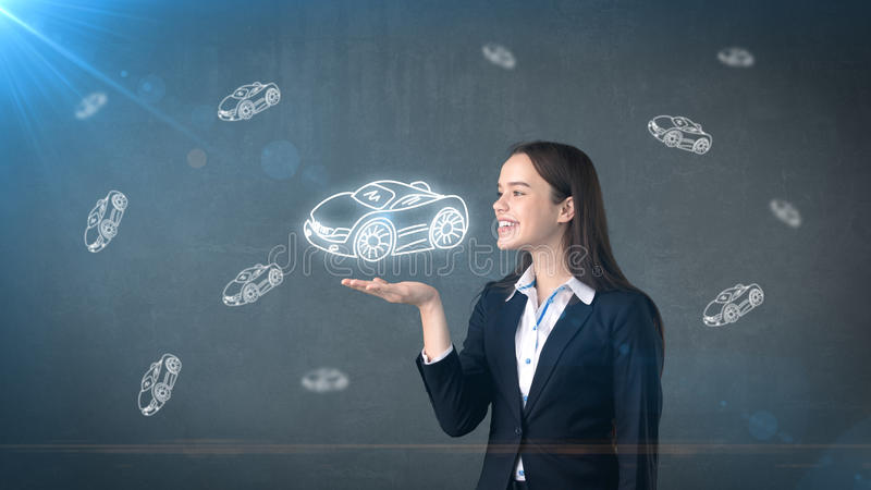 Portrait of young woman holding painted cartoon car on the open hand palm, drawn studio background. Business concept. Portrait of young beautiful longhair woman royalty free stock photography