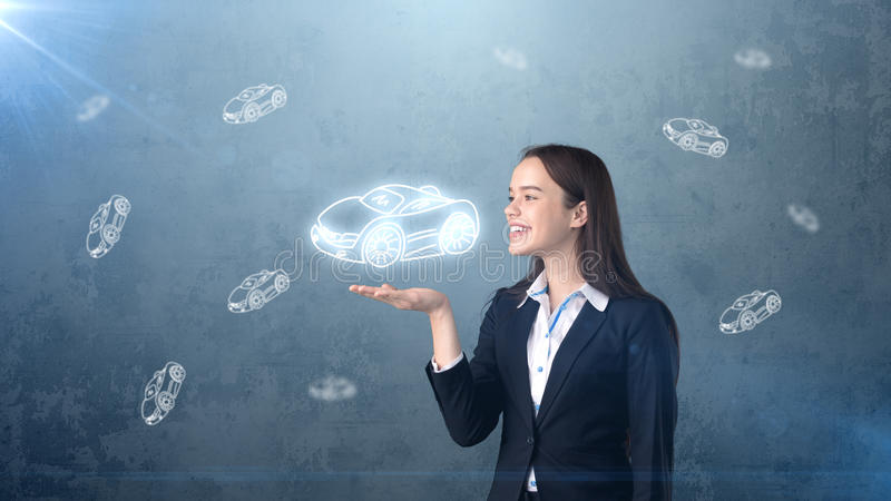 Portrait of young woman holding painted cartoon car on the open hand palm, drawn studio background. Business concept. Portrait of young beautiful longhair woman stock photos
