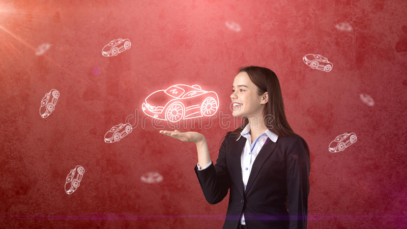 Portrait of young woman holding painted cartoon car on the open hand palm, drawn studio background. Business concept. Portrait of young beautiful longhair woman royalty free stock images