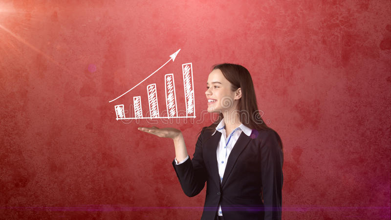Portrait of young woman holding white painted growing chart on the open hand palm, isolated background. Business concept stock photography