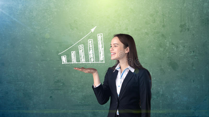 Portrait of young woman holding white painted growing chart on the open hand palm, isolated background. Business concept stock images