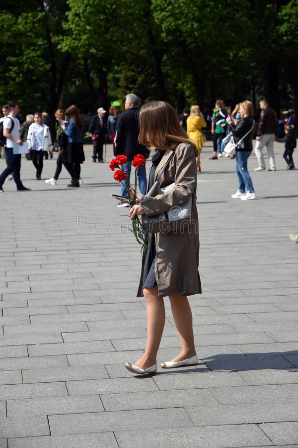 Portrait of a young woman she holds red carnations. Victory day celebrations in Moscow, May 09, 2019, Gorky park. It is a tradition - to give carnation flowers stock photo