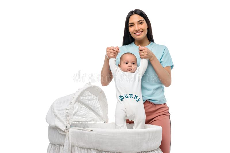 Portrait of young woman and infant baby in crib. Isolated on white royalty free stock photo