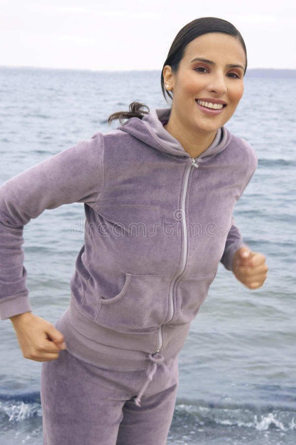 Portrait of a young woman jogging at the sea front. Portrait of a young woman wearing a tracksuit, jogging at the sea front stock image