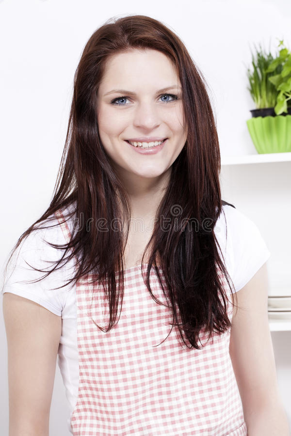 Portrait of a young woman in kitchen stock photo