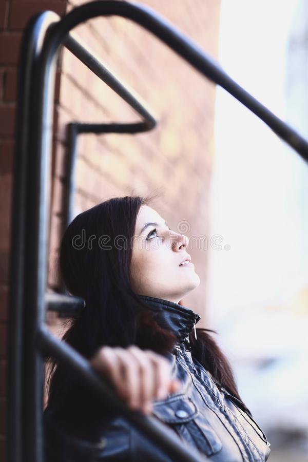 Portrait of a young woman leaning against a wall of a city building royalty free stock image