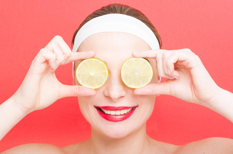 Portrait of young woman with lemon on eyes royalty free stock image