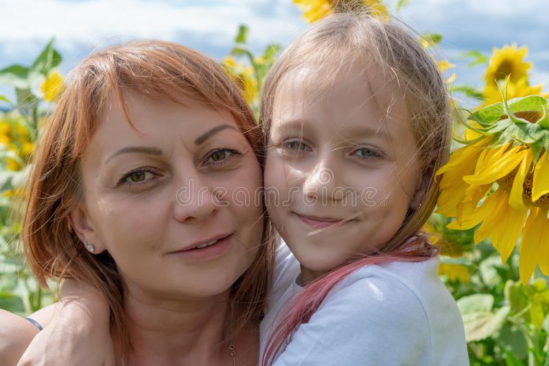 Portrait of a young woman and little girl outdoors.Sweet little girl is hugging her beautiful young mom standing in a large field stock photography