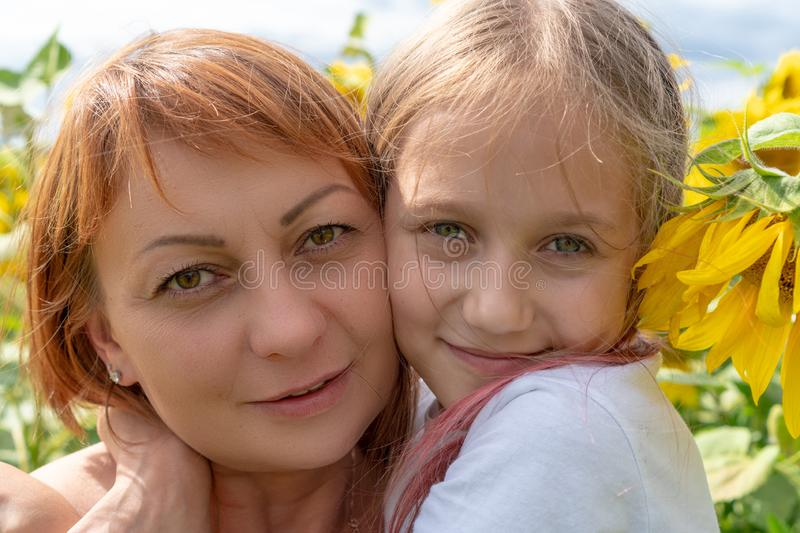 Portrait of a young woman and little girl outdoors.Sweet little girl is hugging her beautiful young mom standing in a large field royalty free stock photography