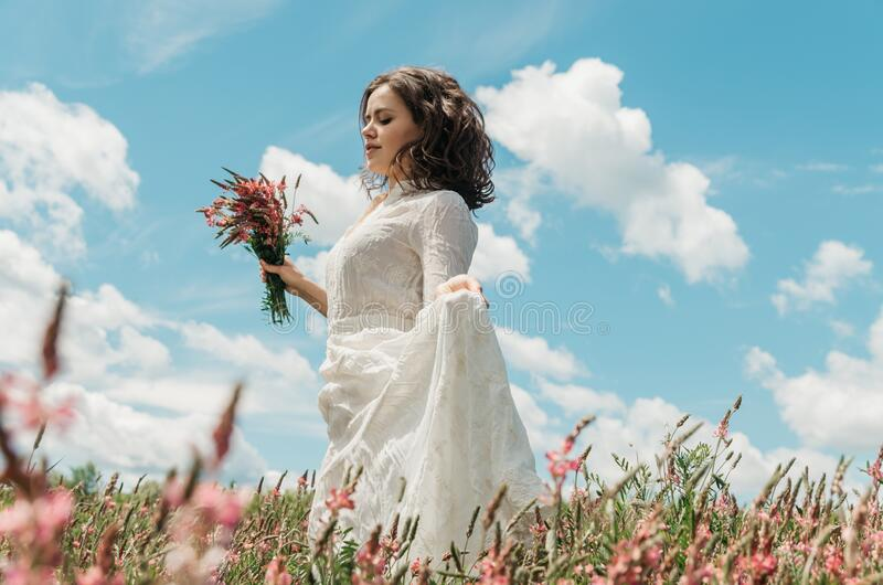 Portrait of a young woman in a long white dress holding a flower bouquet. And her dress as she walks in a flower field against blue sky royalty free stock photo