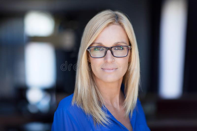 Portrait Of A Young Woman looking at the camera. She wears glasses royalty free stock photography