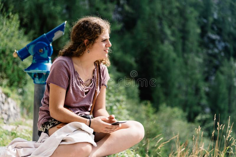 Portrait of young woman looking at landscape and sitting in view stock image