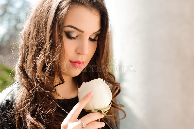 Portrait of young woman in love with rose in hands royalty free stock images