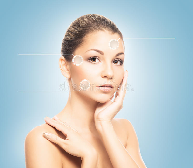 Portrait of a young woman in makeup with arrows. Close-up portrait of young, fresh and natural woman with the dotted arrows (spa, surgery, face lifting and make royalty free stock photos