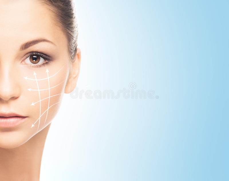 Portrait of a young woman in makeup on a blue background. Close-up portrait of young, fresh and natural woman with the dotted arrows royalty free stock photo