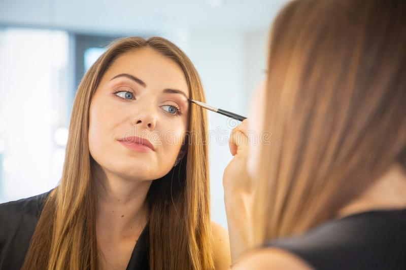 Portrait of young woman making make-up near mirror royalty free stock image