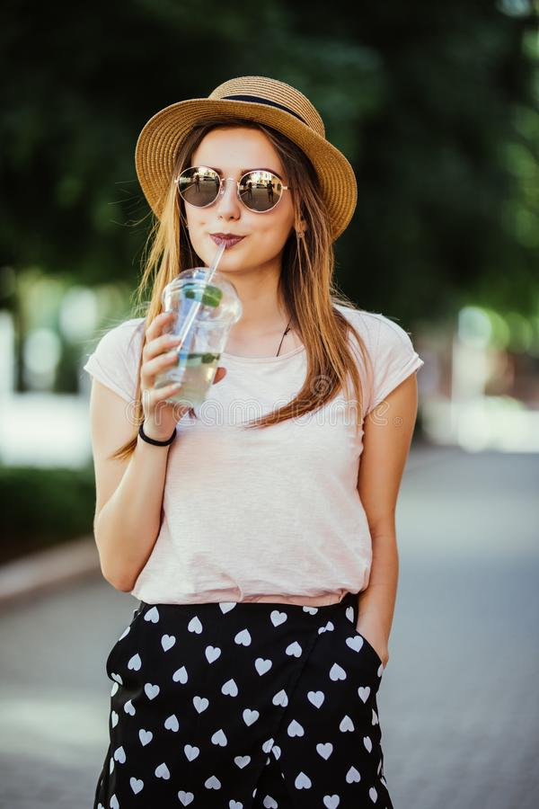 Portrait of young woman with mojito resting on city street summer stock photos