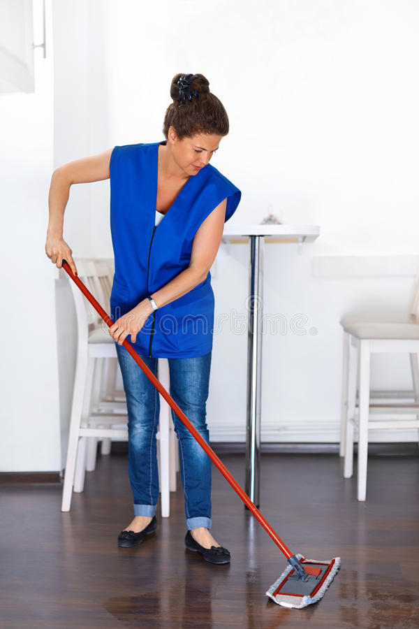 Portrait Of Young Woman Mopping Floor At Home . Cleaning Sevice royalty free stock photos