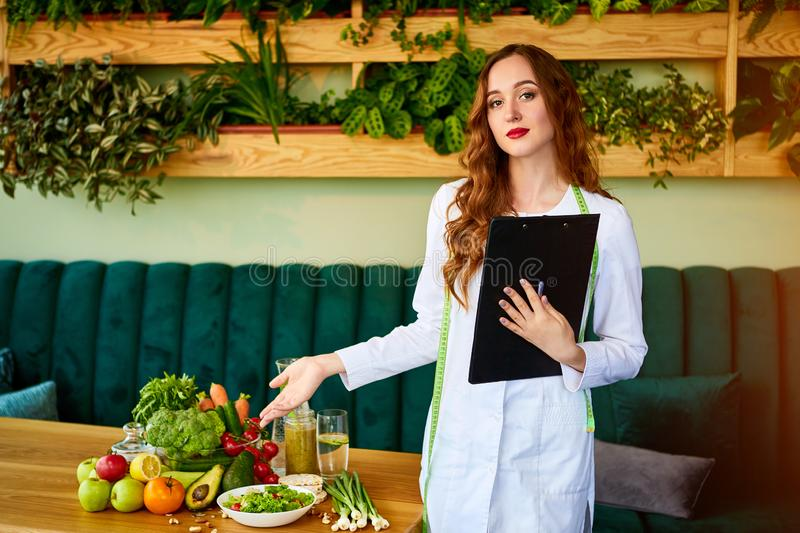 Portrait of a young woman nutritionist in medical gown standing with clipboard and tape measure in the office with healthy food on stock photography
