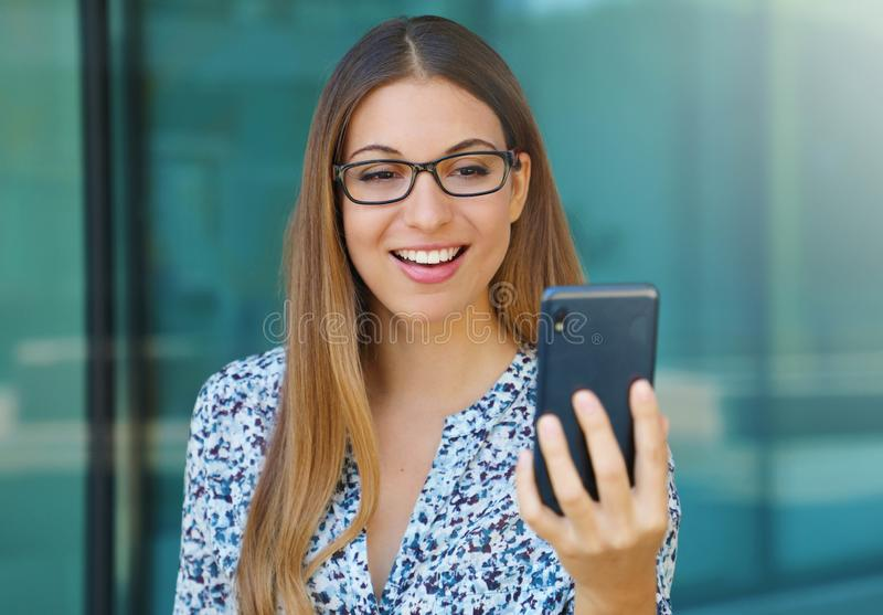 Portrait of young woman outdoor making a video call using smart phone stock photos