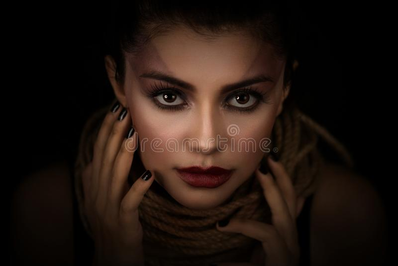 Portrait of young woman over rope with black background. Fashion, extraordinary makeup and face lifting concept. Portrait of young woman over rope with black stock photo