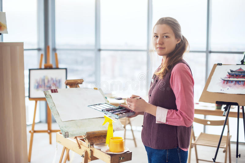 Portrait of a young woman painter drawing with watercolor palette on paper using easel. Portrait of a young woman painter drawing with watercolor palette on stock photography