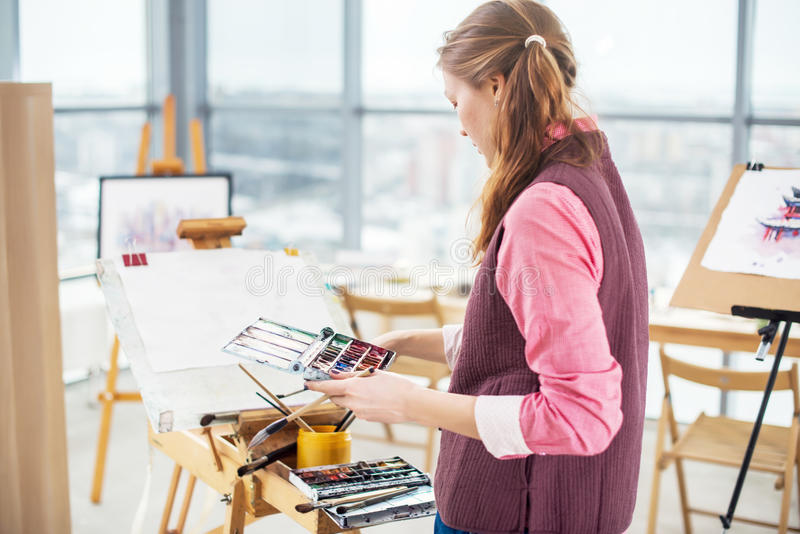 Portrait of a young woman painter drawing with watercolor palette on paper using easel. Portrait of a young woman painter drawing with watercolor palette on stock photos