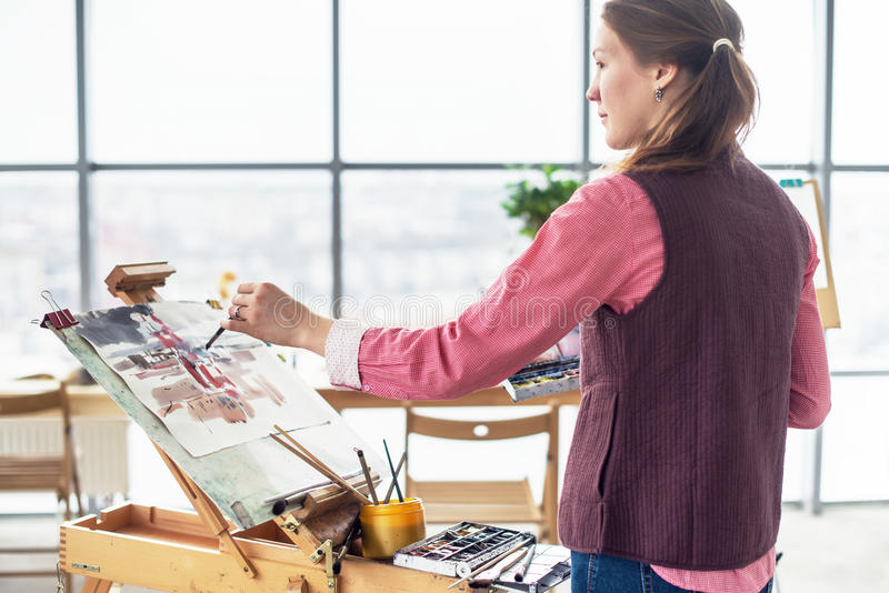 Portrait of a young woman painter drawing with watercolor palette on paper using easel. Portrait of a young woman painter drawing with watercolor palette on stock photo