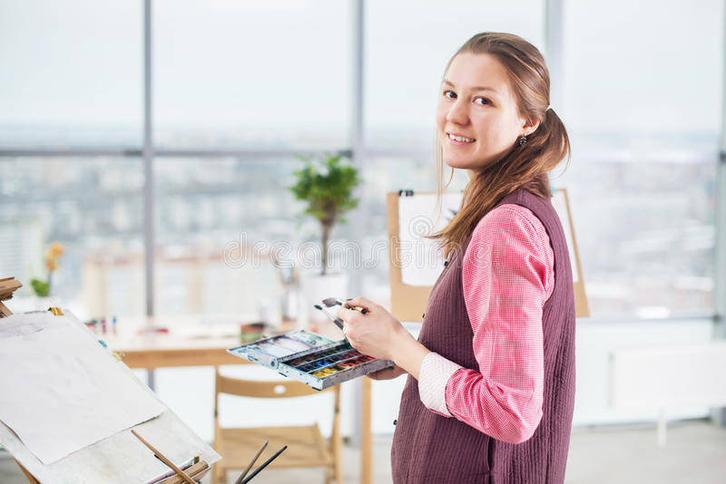 Portrait of a young woman painter drawing with watercolor palette on paper using easel. stock photo