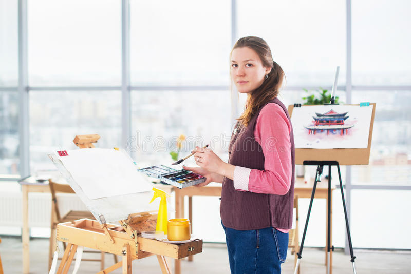 Portrait of a young woman painter drawing with watercolor palette on paper using easel. royalty free stock photography