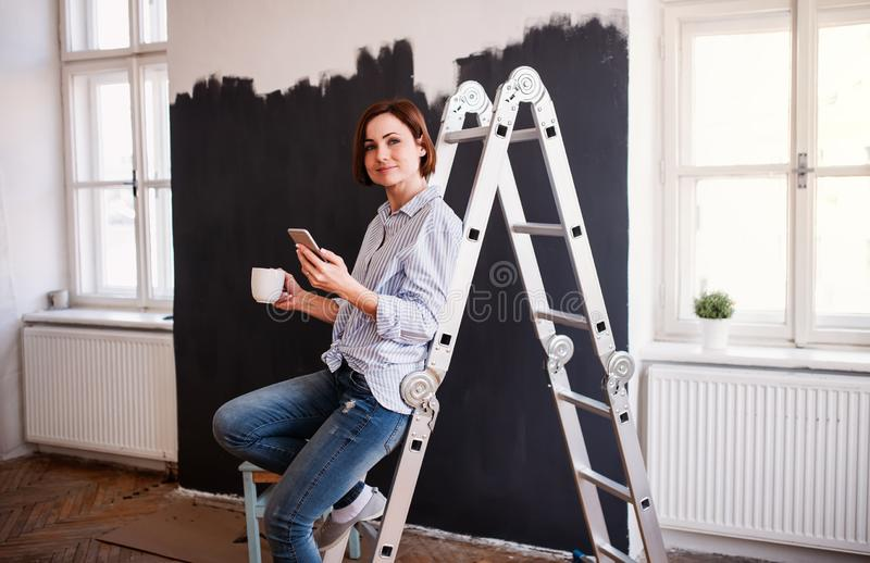 A portrait of young woman painting wall black. A startup of small business. A portrait of young creative woman with a cup of coffee and smartphone painting wall royalty free stock photos