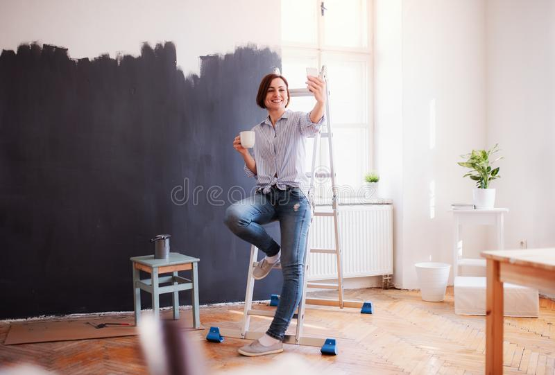 A portrait of young woman painting wall black. A startup of small business. stock photo
