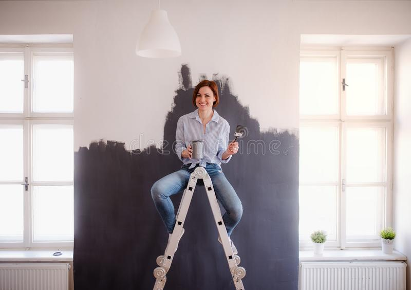 A portrait of young woman painting wall black. A startup of small business. royalty free stock images