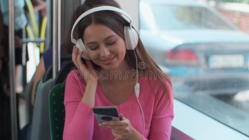 Portrait of a young woman passenger enjoying trip at the public transport, sitting with headphones in the modern tram. Portrait of a young woman passenger stock photo