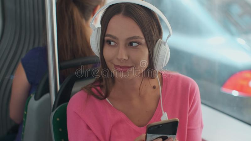 Portrait of a young woman passenger enjoying trip at the public transport, sitting with headphones in the modern tram. Portrait of a young woman passenger stock image