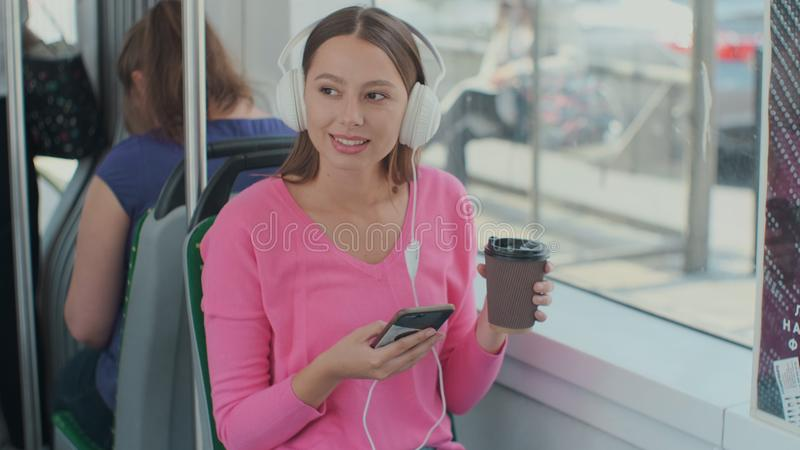 Portrait of a young woman passenger enjoying trip at the public transport, sitting with headphones in the modern tram. Portrait of a young woman passenger royalty free stock images