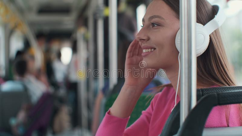 Portrait of a young woman passenger enjoying trip at the public transport, sitting with headphones in the modern tram. Portrait of a young woman passenger royalty free stock photos