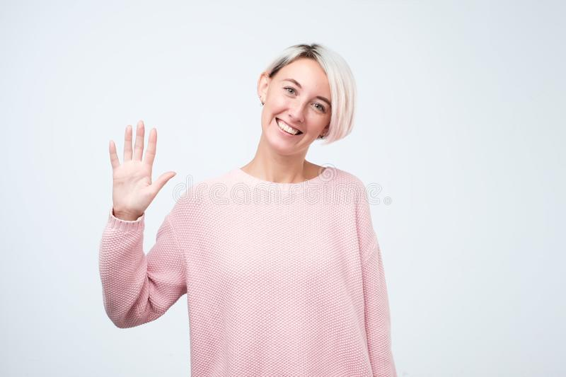 Portrait of a young woman in pink sweater smiling and saying hello stock image