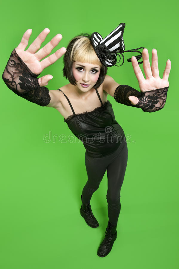 Portrait of young woman posing with fingerless gloves and headdress over green background stock images