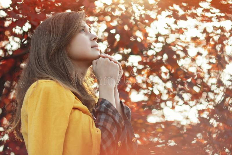 Portrait of a young woman praying in nature, the girl thanks God with her hands folded at her chin, a conversation with the stock photography