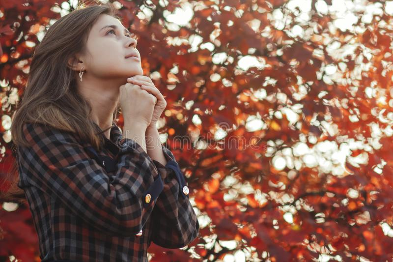 Portrait of a young woman praying in nature, the girl thanks God with her hands folded at her chin, a conversation with the stock photo