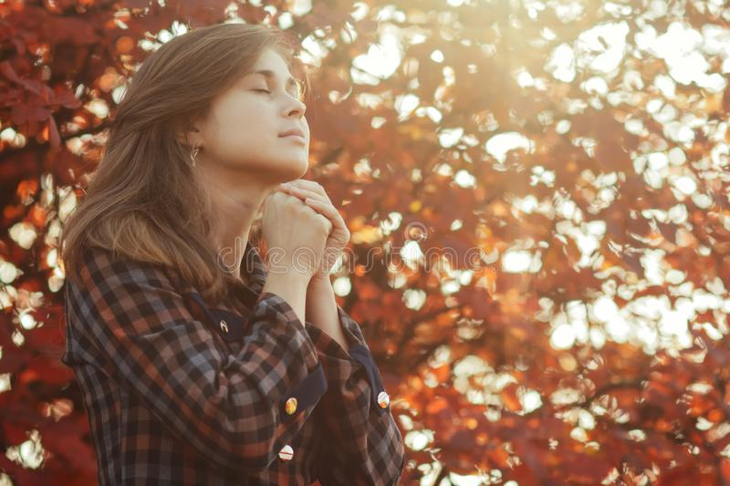 Portrait of a young woman praying in nature, the girl thanks God with her hands folded at her chin, a conversation with the royalty free stock photo